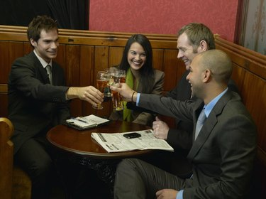 Woman and three male colleagues toasting each other in bar, smiling