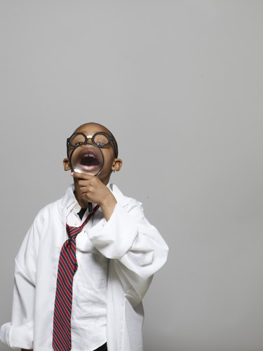 Boy (5-7) in lab coat, holding magnifying glass, opening mouth wide
