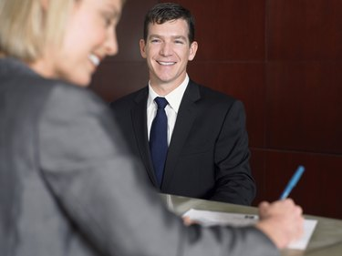 Businesswoman Smiles as She Signs a Document at a Reception Desk