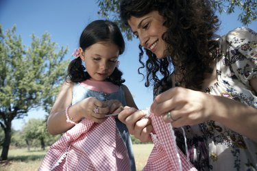 mother and daughter sewing outdoors