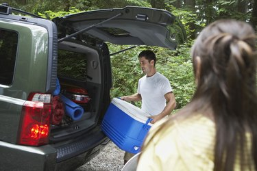 Couple loading car in countryside