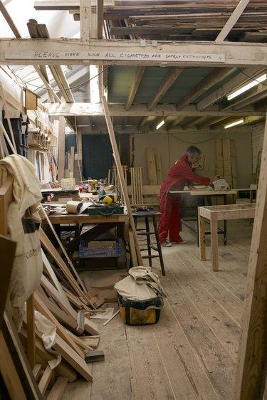carpenter working in his workshop cutting wood