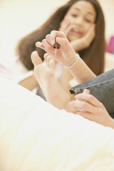 Teenager polishing her toenails
