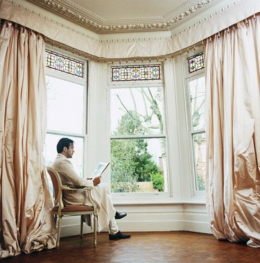 Young Man Sitting in a Chair by a Window at Home Reading a Newspaper