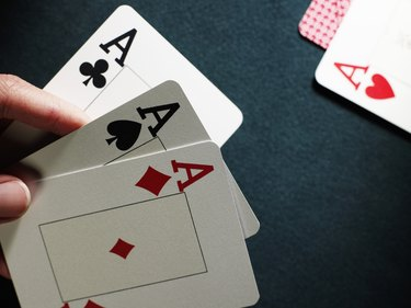 Man holding three aces, close-up