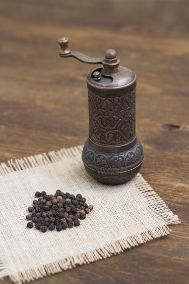 Vintage turkish pepper mill and black peppercorns