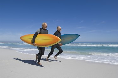 Surfers running on beach in wetsuits