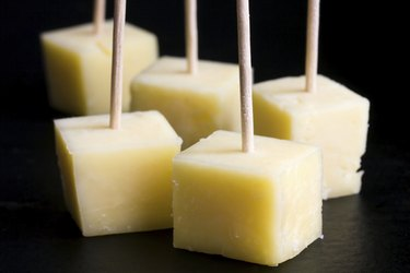 Cubes of yellow cheese on toothpicks. Black background.