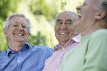 Three senior men laughing, close-up (focus on man wearing glasses)