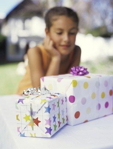 Girl (9-11) looking at gifts, close up