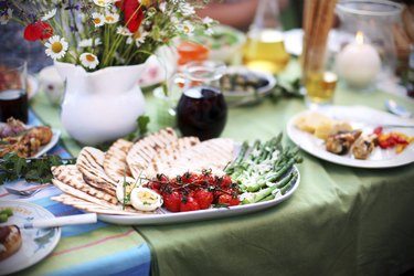 Grilled asparagus and tomatoes with pita bread on picnic table