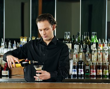 Bartender pouring cocktail behind bar