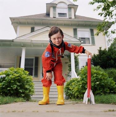 Boy (3-5) in yellow wellington boots, hand on toy rocket, portrait