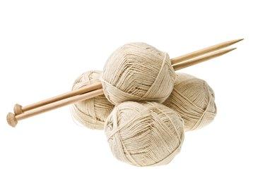 Knitting balls and knitting needles isolated on white.