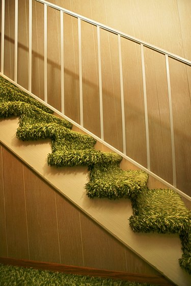 Stairs to the second floor with metal bannister and green shag carpet.