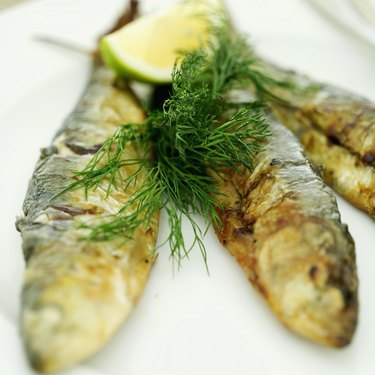 Close-up of whole fried fish garnished with chives and a lemon half