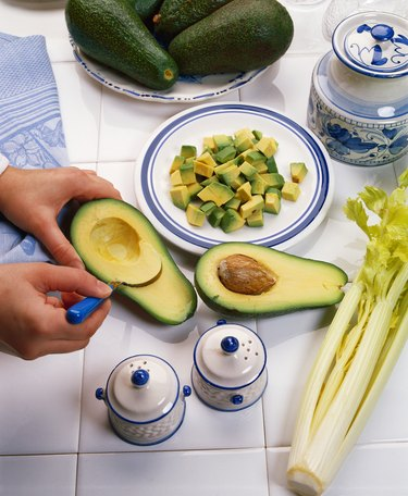 close-up of hands scooping the flesh from an avocado on a tiled counter