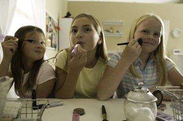Three teenage girls (13-14) applying make-up in friends bedroom