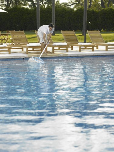 Man cleaning hotel outdoor pool with net