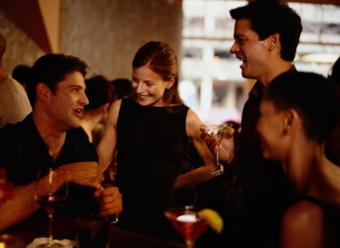 Two couples having cocktails at bar