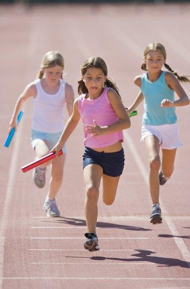 Girls running relay race