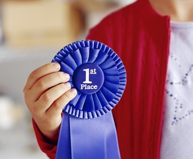 Child holding blue first place ribbon