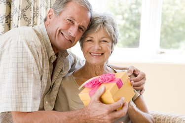 Husband giving wife gift in living room smiling