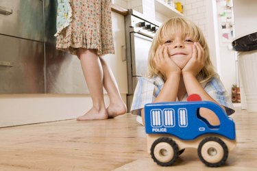Boy on kitchen floor with toy car
