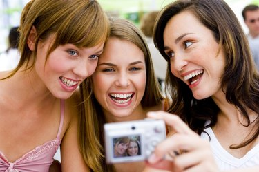 Women taking photograph with digital camera