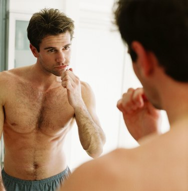 close-up of a man brushing his teeth and looking in the mirror