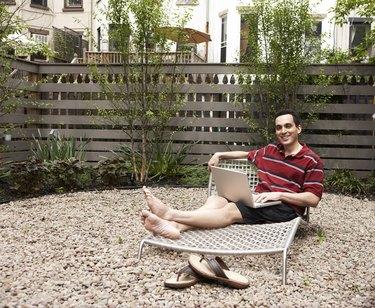 Relaxing on lounge chairs in urban backyard