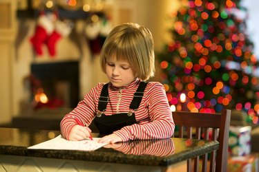 Girl writing Christmas wish list
