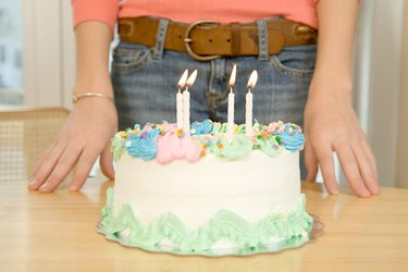Person standing with birthday cake
