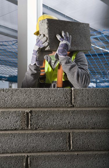 Construction worker building cinderblock wall
