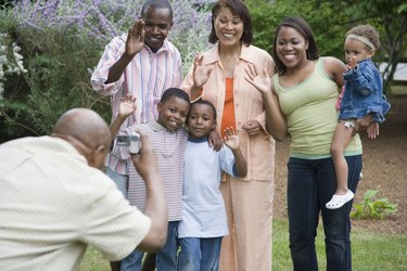 Rear view of a mature man taking a picture of his family members with a digital video camera