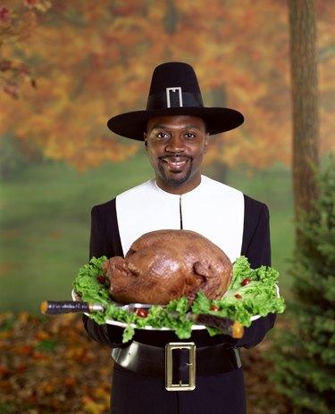 Man in pilgrim costume holding roasted turkey