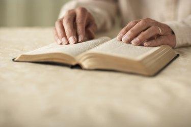 Senior man reading Bible, close-up of hands