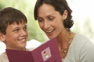 Mother and son (10-12) smiling, card in foreground