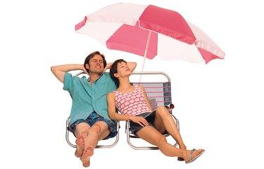 Couple reclining on lounge chairs under beach umbrella