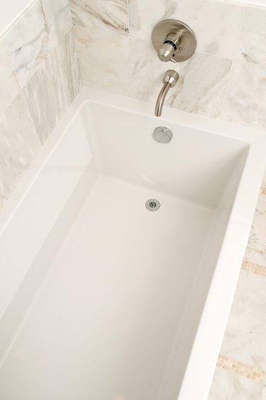 Bathtub in bathroom with marble walls