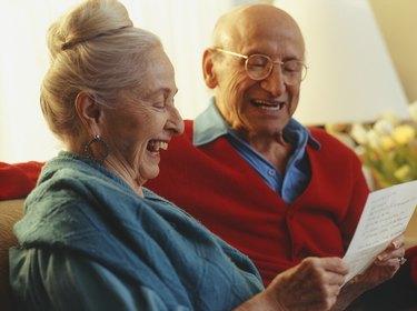 Senior couple reading letter in living room