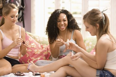 Teenage girls painting nails together
