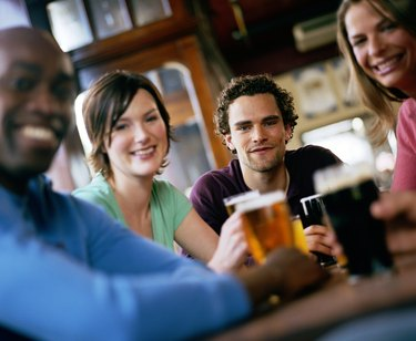 Friends at pub table, smiling, portrait (focus on man in centre)