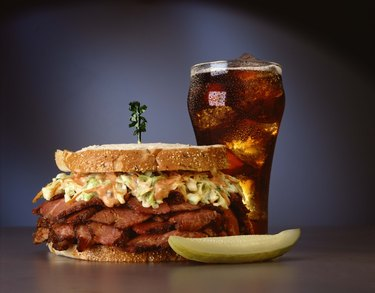 Pastrami sandwich with soft drink and pickle