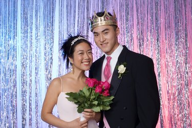 Prom queen holding flowers with king