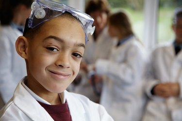Schoolboy (8-10) in science class, smiling, portrait (focus on boy)