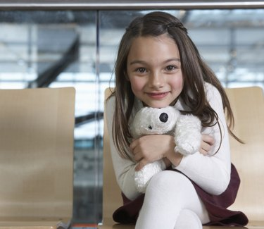 Girl (5-7) sitting in airport hugging soft toy, smiling, portrait