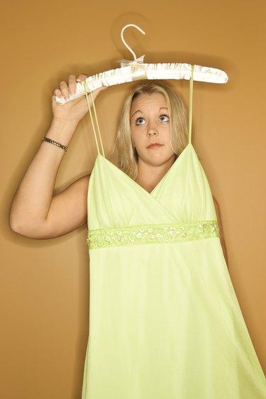 Woman holding dress on hanger