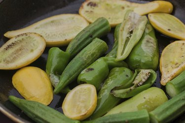 Green pepper, yellow squash and okra being sauteed in pan