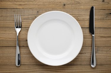 Plate, fork and knife on wood